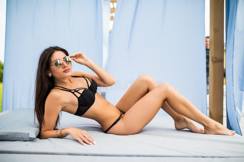 Ursnygg ung kvinna i solglasögon som ligger i chaise-vardagsrum av simbassängen arkivbilder