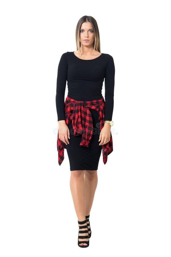 Ursnygg ung kvinna i svart klänning som går och ser kameran arkivbilder