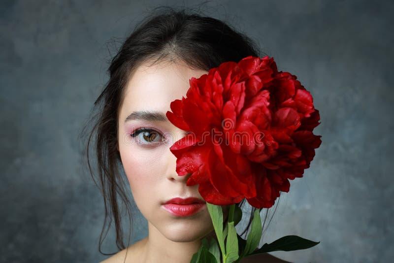 Ursnygg ung kvinna med det ljusa sminket som poserar med pionblommor dofter f?r sk?nhetsmedel f?r tillbeh?rbakgrund vita kosmetis arkivbilder
