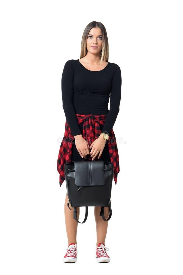 Ursnygg ung kvinna som bär den svarta påsen i båda händer som ser upp royaltyfri foto