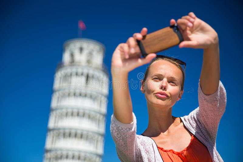 Ursnygg ung kvinna som tar en selfie med hennes smarta telefon arkivbild