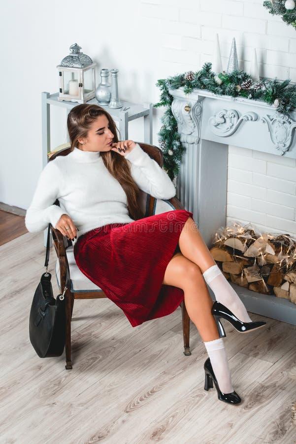 Ursnygg ung kvinnlig i en röd kjol och en vit sweater som sitter i retro fåtölj på en jul dekorerad vägg royaltyfria bilder