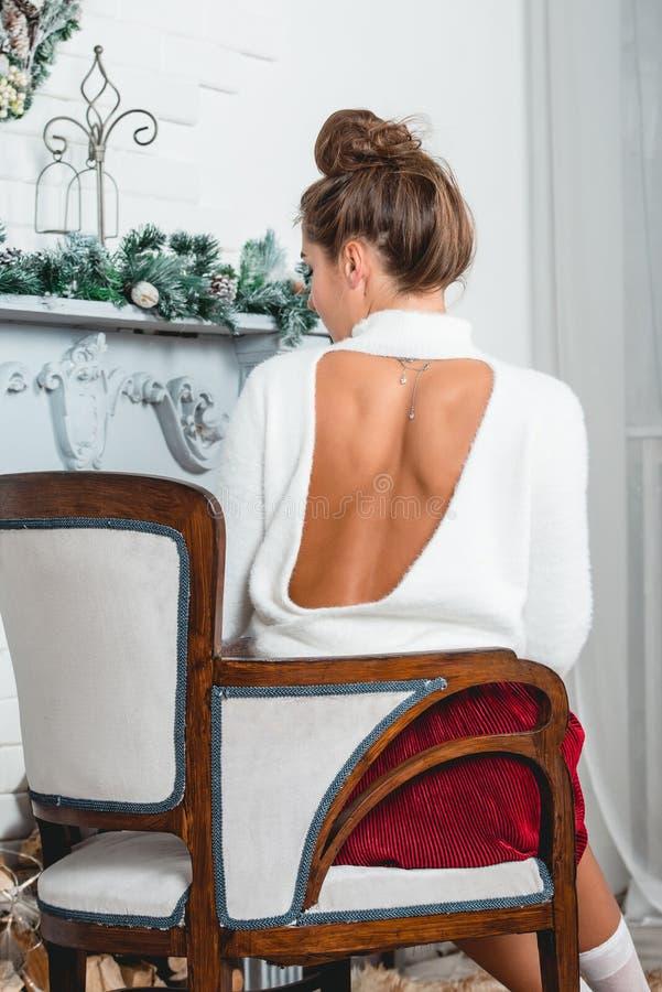 Ursnygg ung kvinnlig i en röd kjol och en vit sweater som sitter i retro fåtölj på en jul dekorerad vägg arkivfoton