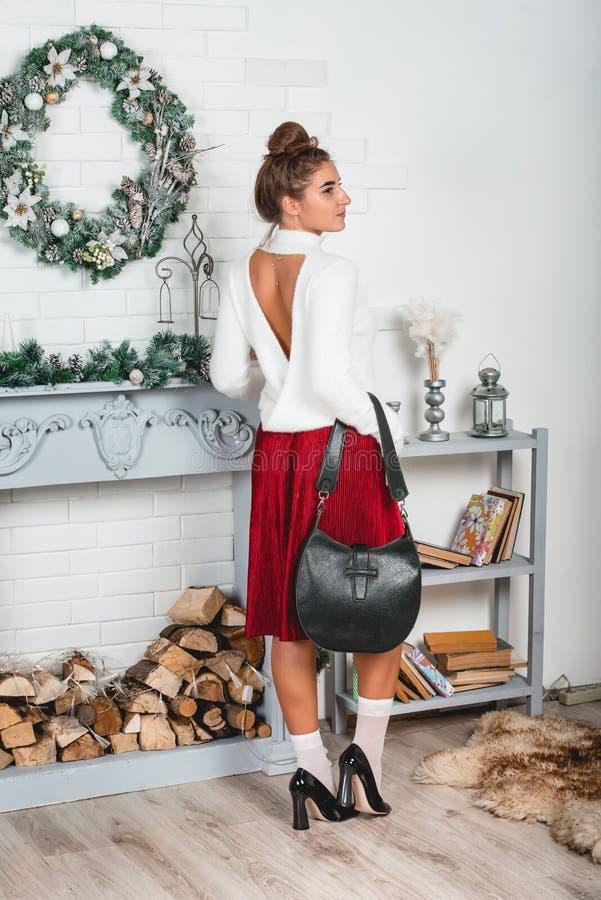 Ursnygg ung kvinnlig i en röd kjol och vitt sweateranseende i ett jul dekorerat rum Erotiska ben i vit royaltyfri fotografi