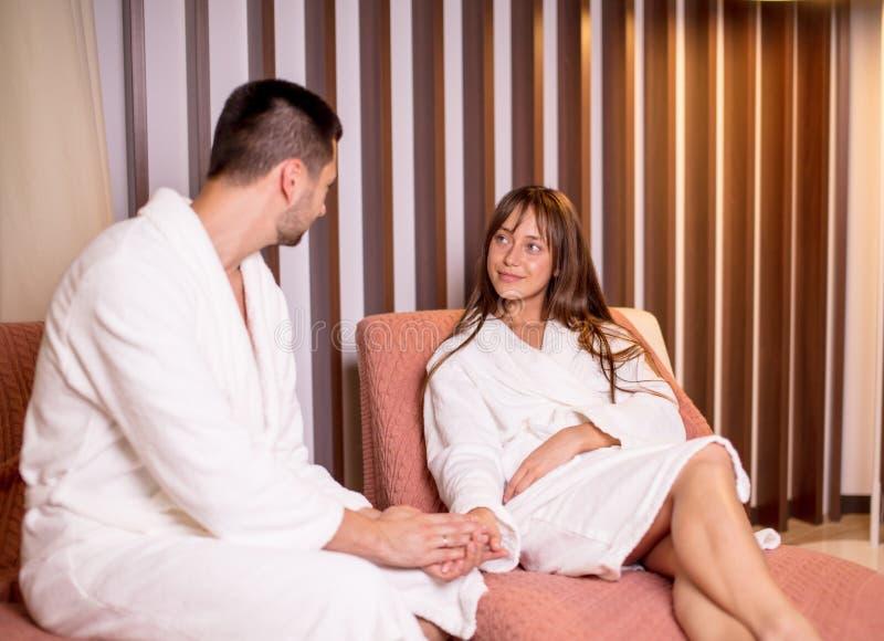 Ursnygg ung man och kvinna som vilar, når att ha tagit en shoer i brunnsortmitten royaltyfri fotografi