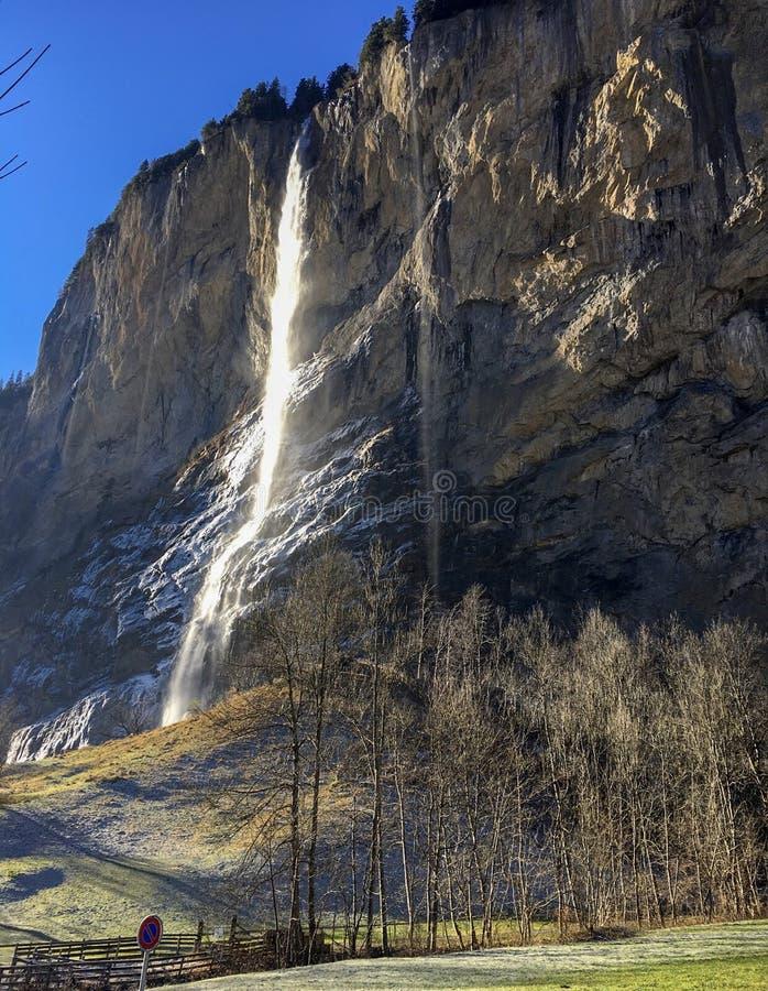 Ursnygg vattenfall på den berömda Lauterbrunnen dalen och schweiziska fjällängar med solljusreflexion i vintersäsong royaltyfri bild