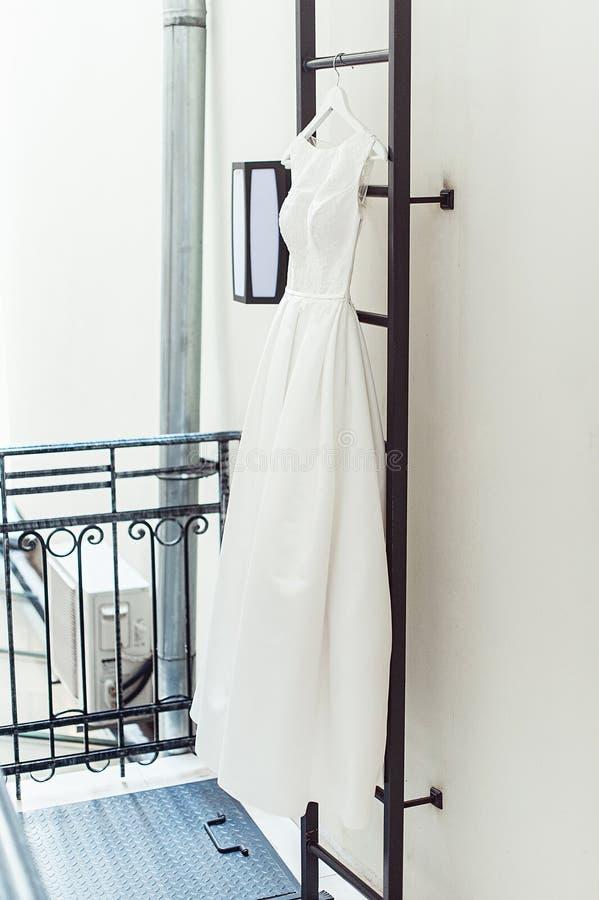Ursnygg vit bröllopsklänning på en brandstege på balkongen brudtillbehör i en bröllopdag arkivfoto