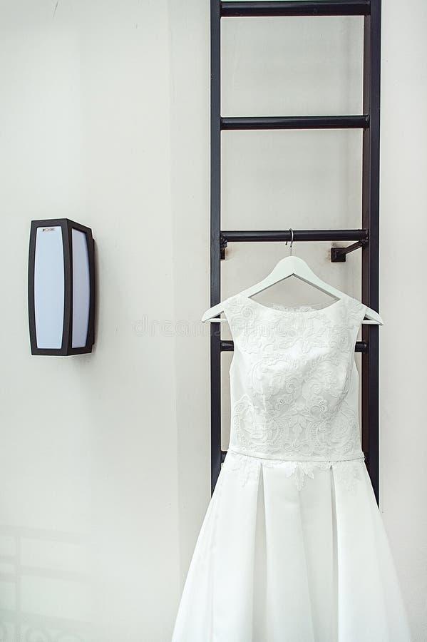 Ursnygg vit bröllopsklänning på en brandstege på balkongen brudtillbehör i en bröllopdag arkivfoton