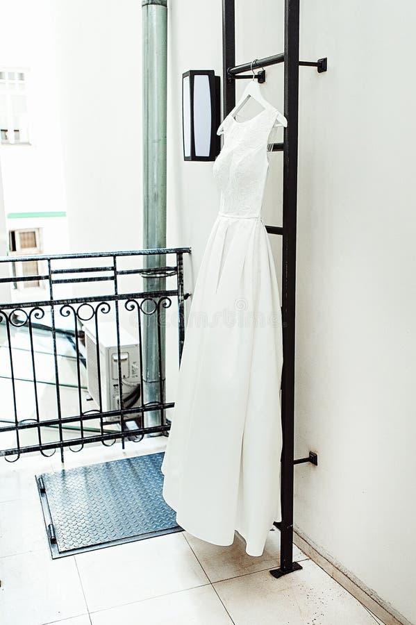 Ursnygg vit bröllopsklänning på en brandstege på balkongen brudtillbehör i en bröllopdag arkivbild