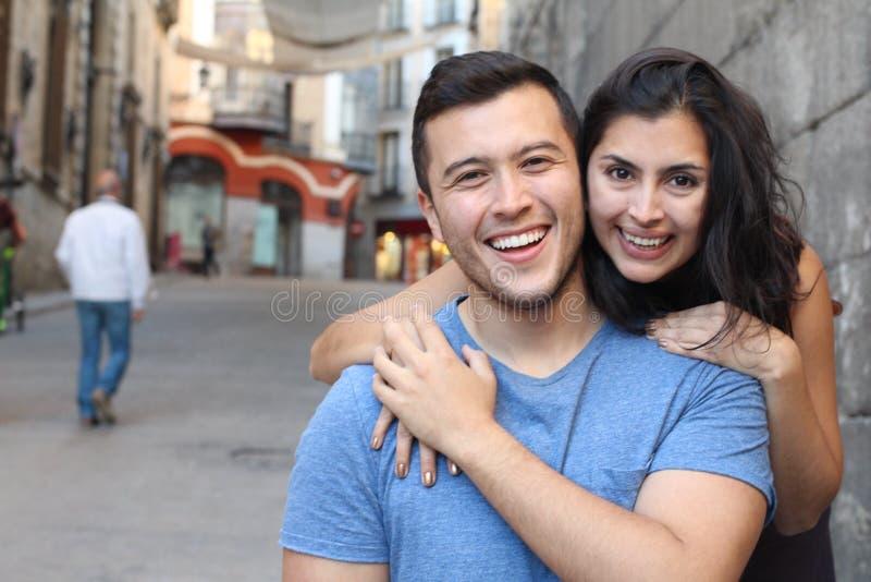 Ursnygga etniska par som tätt ler upp royaltyfria bilder