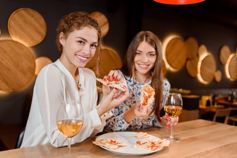 Ursnygga kvinnor som ler, poserar och äter pizza i pizzeria arkivfoton