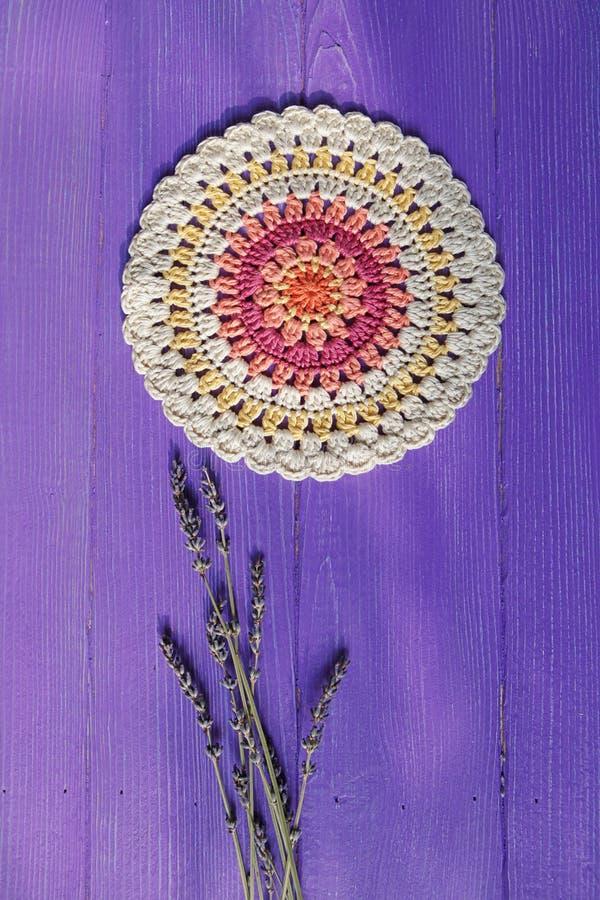 Ursnygga Mandala Crochet Doily och Lavander blommar på lilor R royaltyfri fotografi
