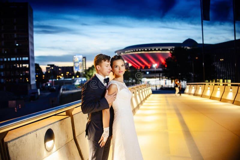 Ursnygga nygifta personer på stadsbron på natten royaltyfri fotografi