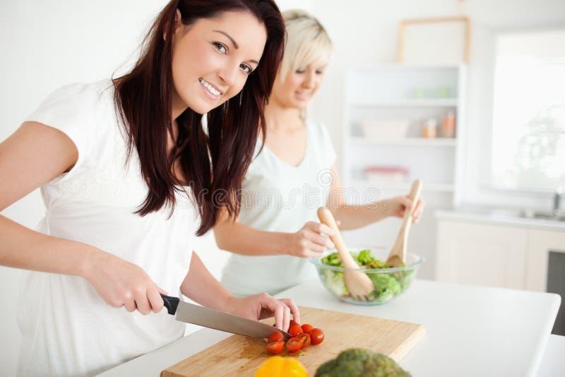 Ursnygga unga kvinnor som förbereder matställe royaltyfri bild