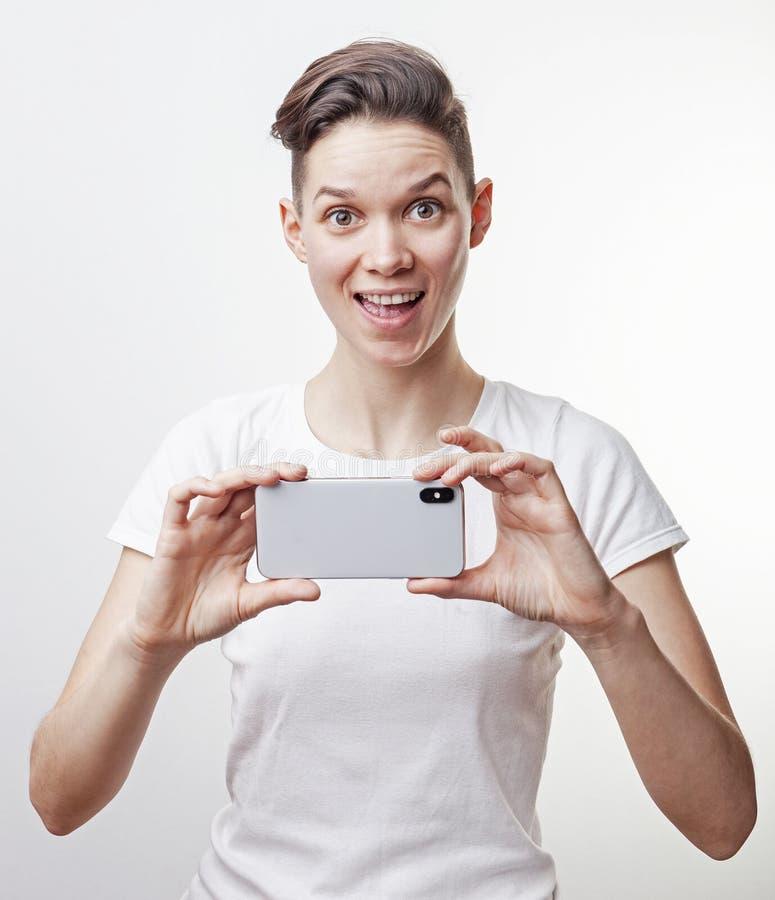 Ursnyggt asiatiskt leende för tonårs- flicka och att ta ett foto genom att använda den främre kameran i hennes smartphone som iso royaltyfri fotografi