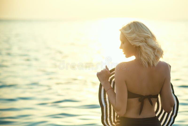 Ursnyggt blont anseende med henne tillbaka till kameran i havsvattnet på soluppgång som rymmer en stor bredbrättad hatt främst av royaltyfria bilder