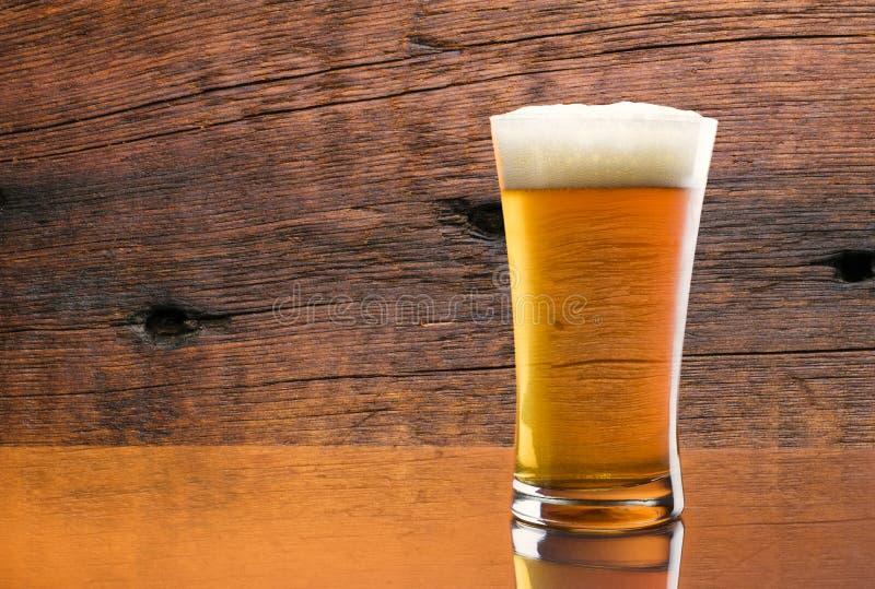 Ursnyggt exponeringsglas av läckert öl med ladugårdträbakgrund arkivfoton