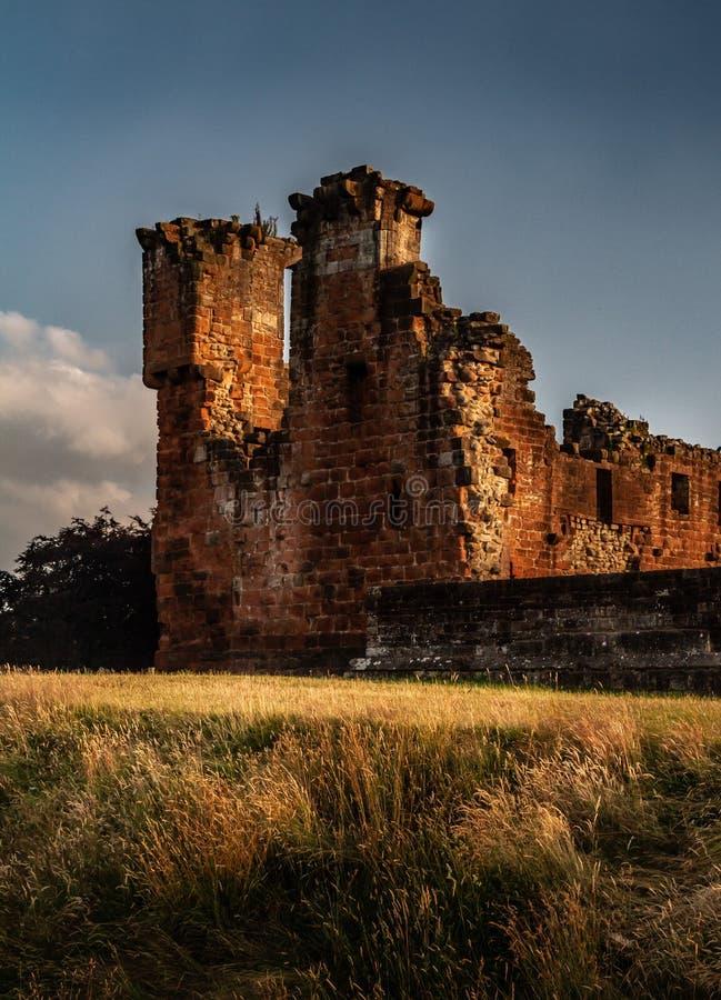 Ursnyggt lynnigt skott av hörndelen och den omgeende väggen av den Penrith slotten på solnedgången i Cumbria, England royaltyfri foto