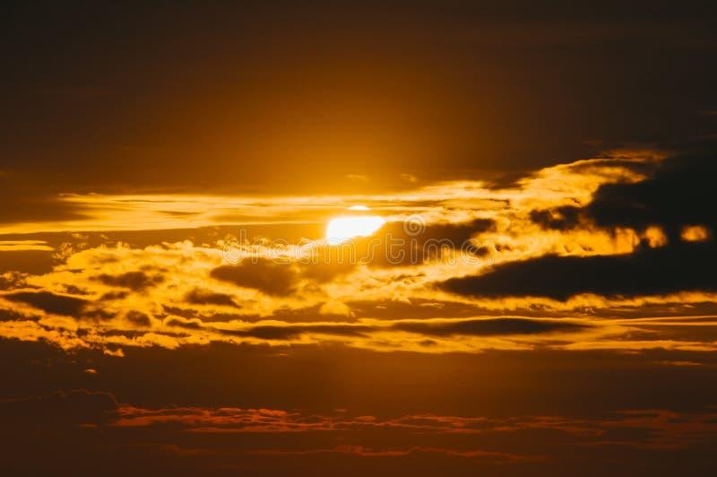 Ursnyggt sceniskt av stark soluppgång med silverfoder och molnet på den orange himlen arkivbild
