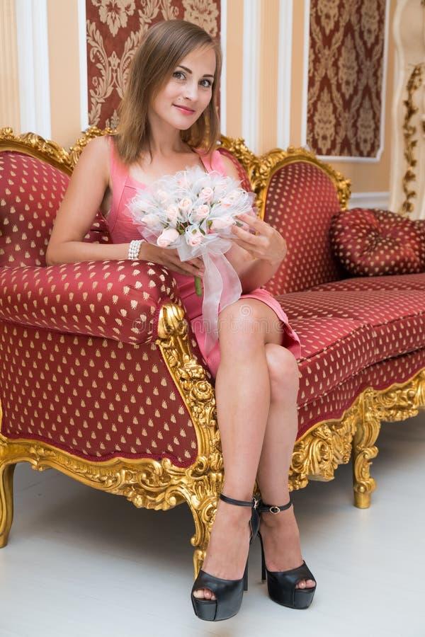 Ursnyggt ung flickasammanträde på den lyxiga soffan och innehav blommar arkivbilder