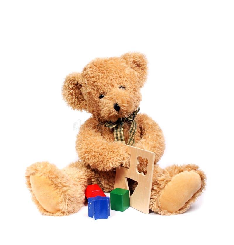 Urso da peluche com brinquedos de madeira imagens de stock