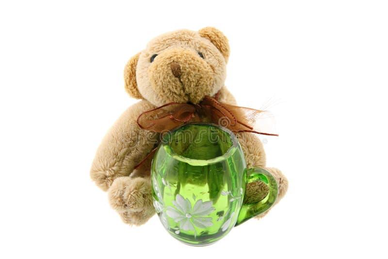 Urso da peluche com um jarro verde isolado no branco fotos de stock