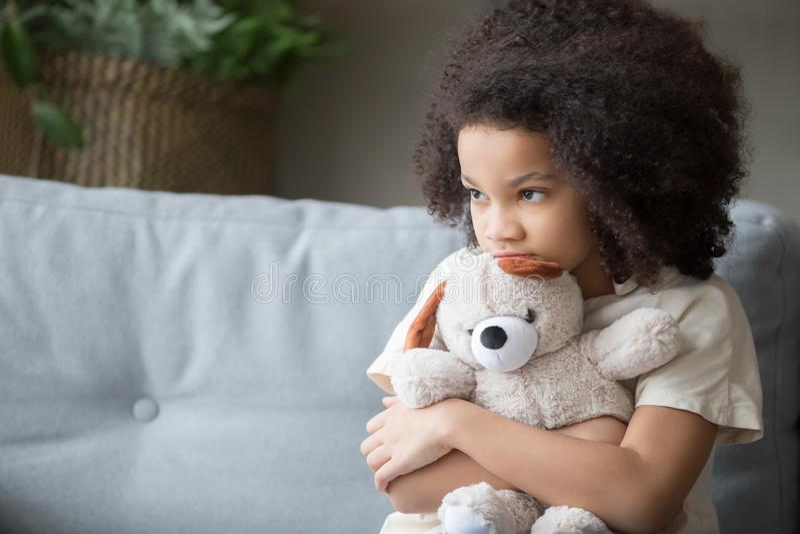 Urso de peluche africano só virado da terra arrendada da menina da criança que olha afastado fotos de stock royalty free