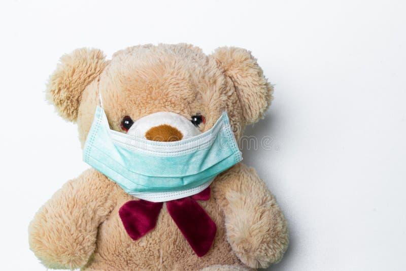 Urso de peluche bonito com máscara protetora em sua boca foto de stock