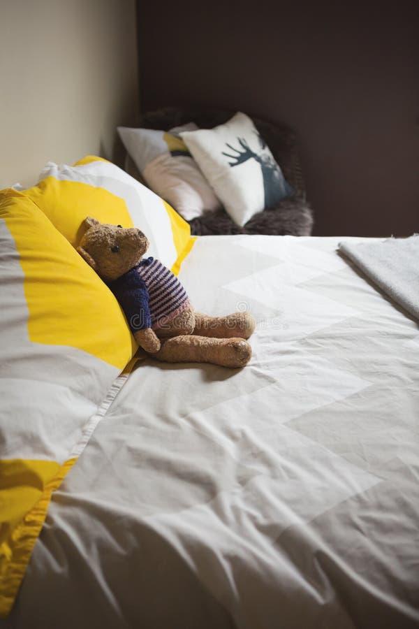 Urso de peluche bonito do brinquedo que senta-se em uma cama do convidado fotografia de stock royalty free