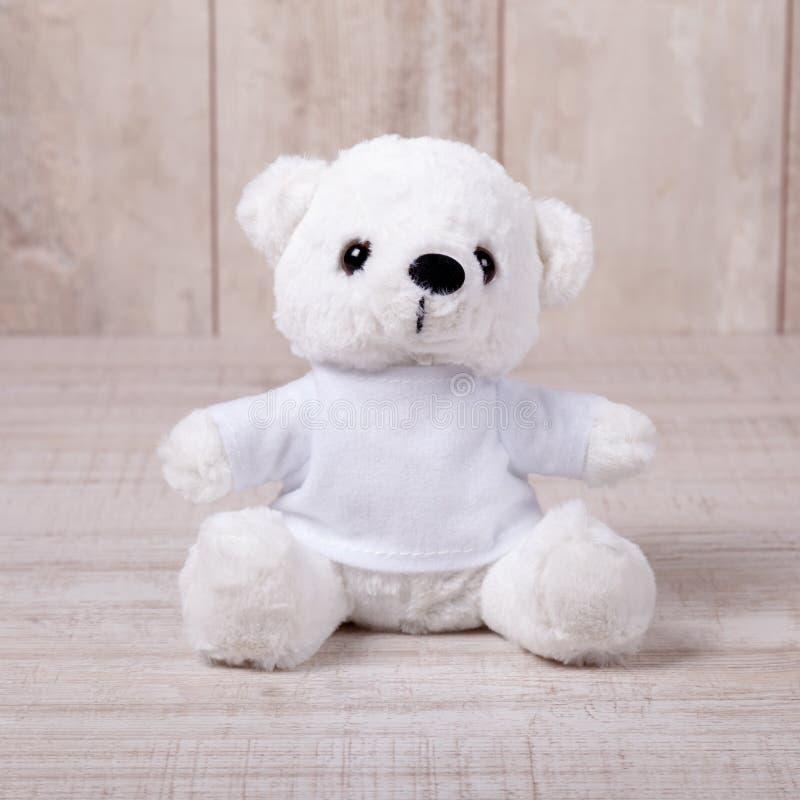 Urso de peluche bonito que senta-se no fundo de madeira velho imagem de stock royalty free