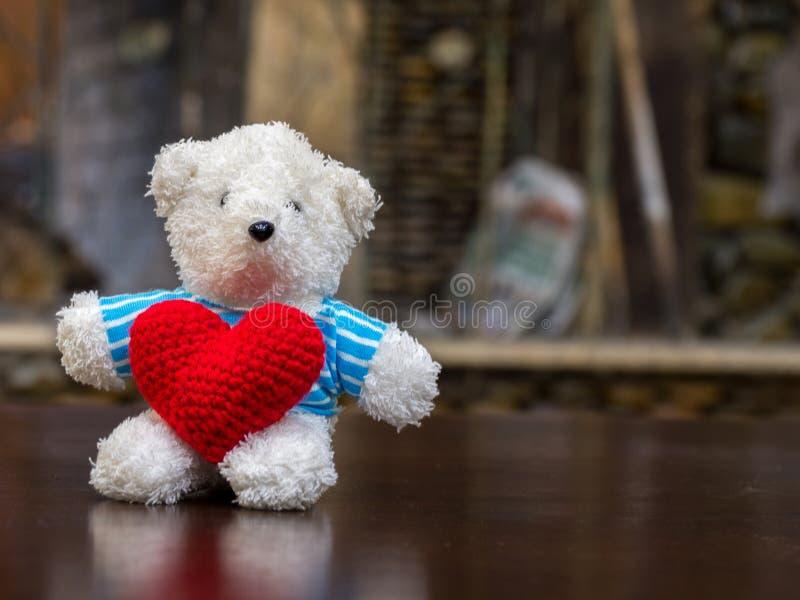 Urso de peluche branco que veste o coração vermelho da posse azul da camisa e que senta-se na tabela de madeira na frente do espa fotografia de stock royalty free
