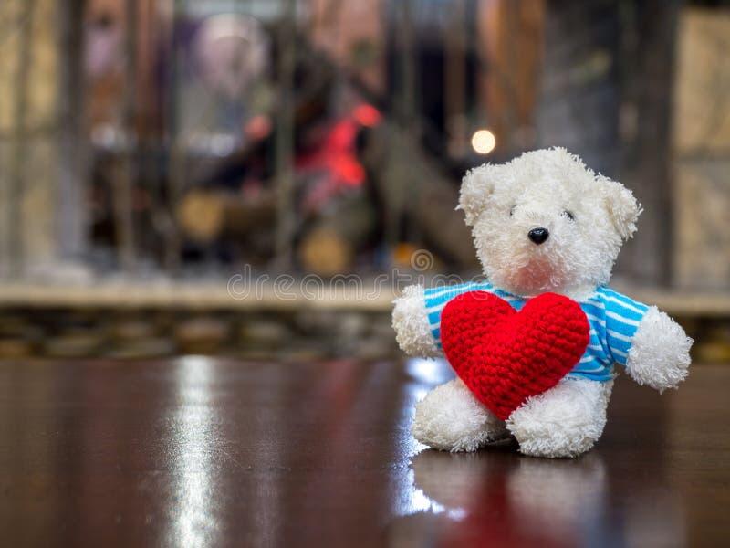 Urso de peluche branco que veste o coração vermelho da posse azul da camisa e que senta-se na tabela de madeira na frente do espa imagem de stock royalty free