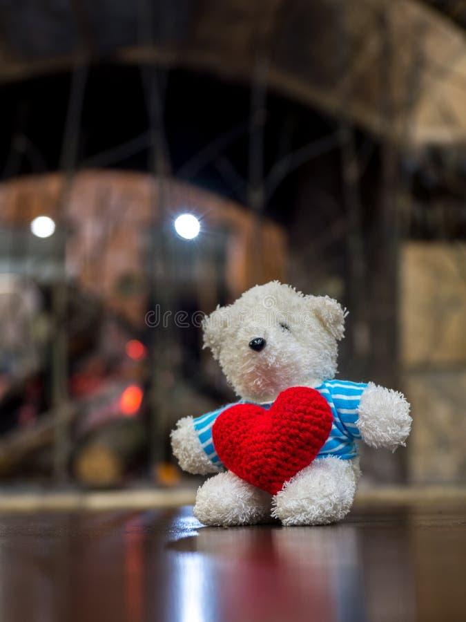 Urso de peluche branco que veste o coração vermelho da posse azul da camisa e que senta-se na tabela de madeira na frente do espa imagens de stock royalty free