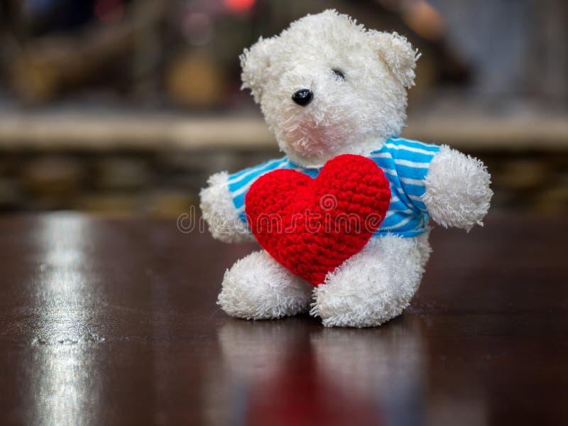 Urso de peluche branco que veste o coração vermelho da posse azul da camisa e que senta-se na tabela de madeira na frente do espa imagens de stock