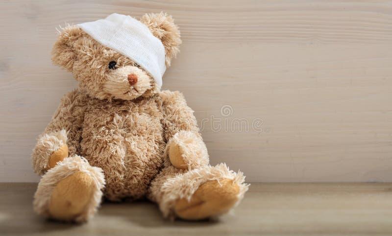 Urso de peluche com atadura em um assoalho de madeira imagem de stock royalty free