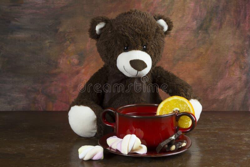 Urso de peluche com a caneca do chá na tabela imagens de stock