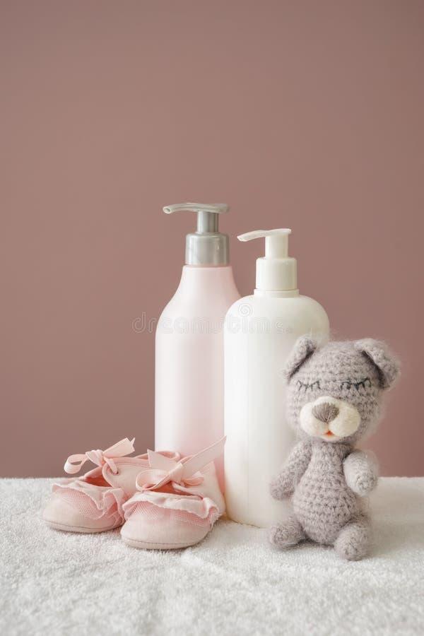 Urso de peluche com sapatas e cosméticos para o bebê na toalha macia contra o fundo da cor fotografia de stock