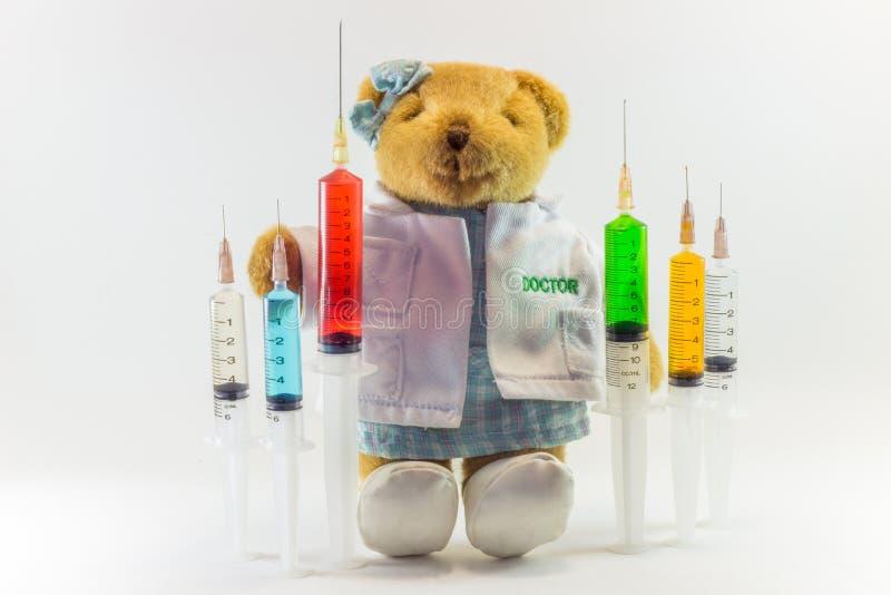 Urso de peluche como um doutor da mulher com as seringas médicas plásticas que contêm soluções multicoloridos e o fundo branco `  fotos de stock