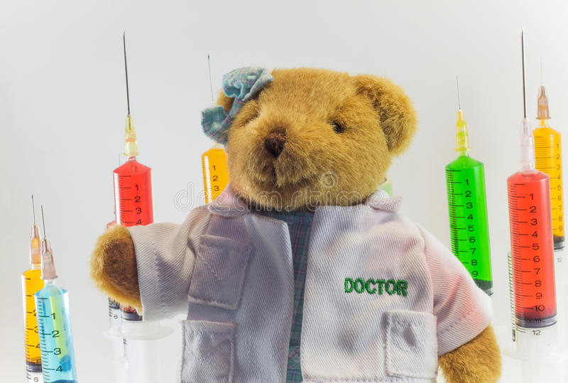 Urso de peluche como um doutor da mulher com as seringas médicas plásticas que contêm soluções multicoloridos e o fundo branco `  foto de stock royalty free
