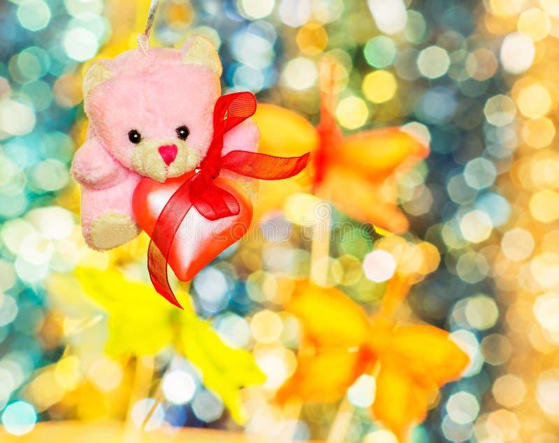 Urso de peluche cor-de-rosa com coração cor-de-rosa no bokeh do fundo fotografia de stock royalty free