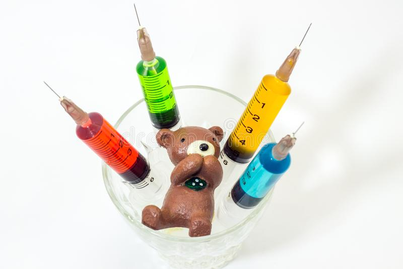 Urso de peluche cozido da argila com as seringas plásticas que contêm soluções multicoloridos imagem de stock