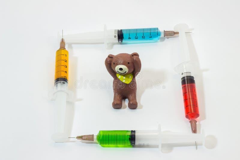 Urso de peluche cozido da argila com as seringas plásticas que contêm soluções multicoloridos fotos de stock royalty free