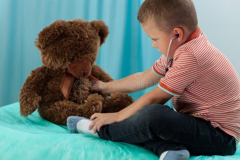 Urso de peluche de exame do menino pelo estetoscópio fotos de stock