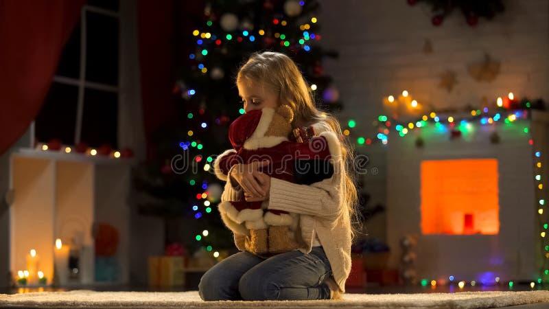 Urso de peluche do abraço da menina da virada, criança abandonada no orfanato no Natal fotografia de stock