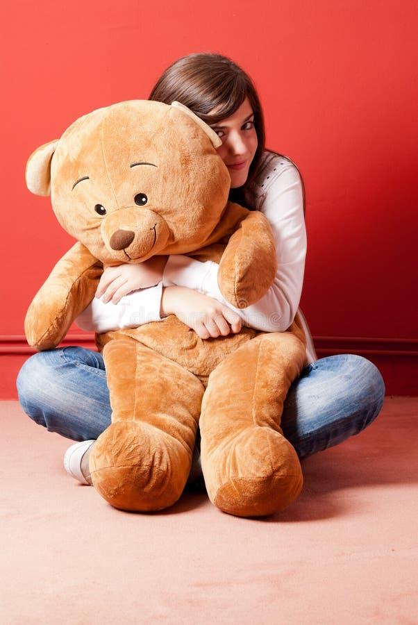 Urso de peluche do abraço da mulher nova que senta-se no assoalho fotos de stock