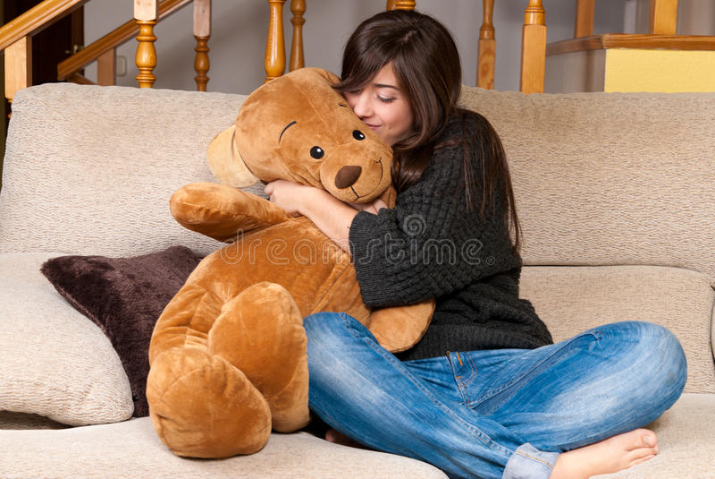 Urso de peluche do abraço da mulher nova que senta-se no sofá fotografia de stock