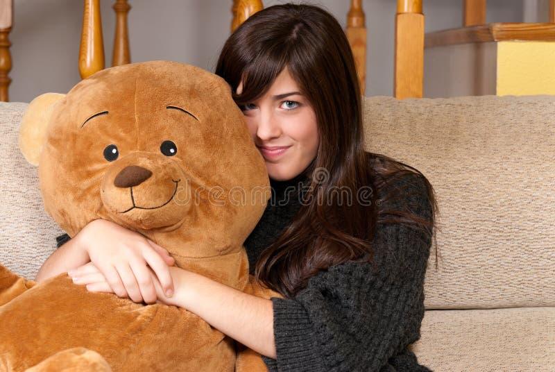 Urso de peluche do abraço da mulher nova que senta-se no sofá foto de stock royalty free