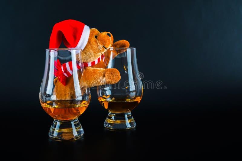 Urso de peluche do Natal com vidro do único uísque de malte, símbolo o fotografia de stock royalty free