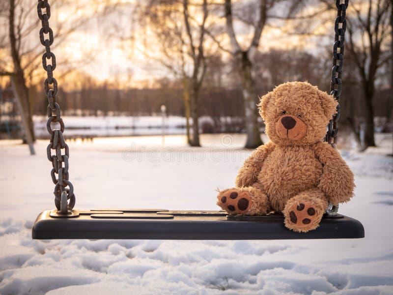 Urso de peluche em um balanço em um lago imagens de stock