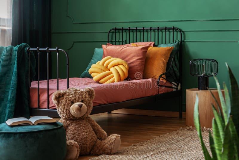 Urso de peluche grande e um livro aberto em um verde, pufe de veludo na frente de uma cama do quadro do metal no interior do quar imagem de stock